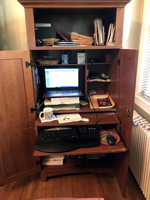 cluttery desk in a corner