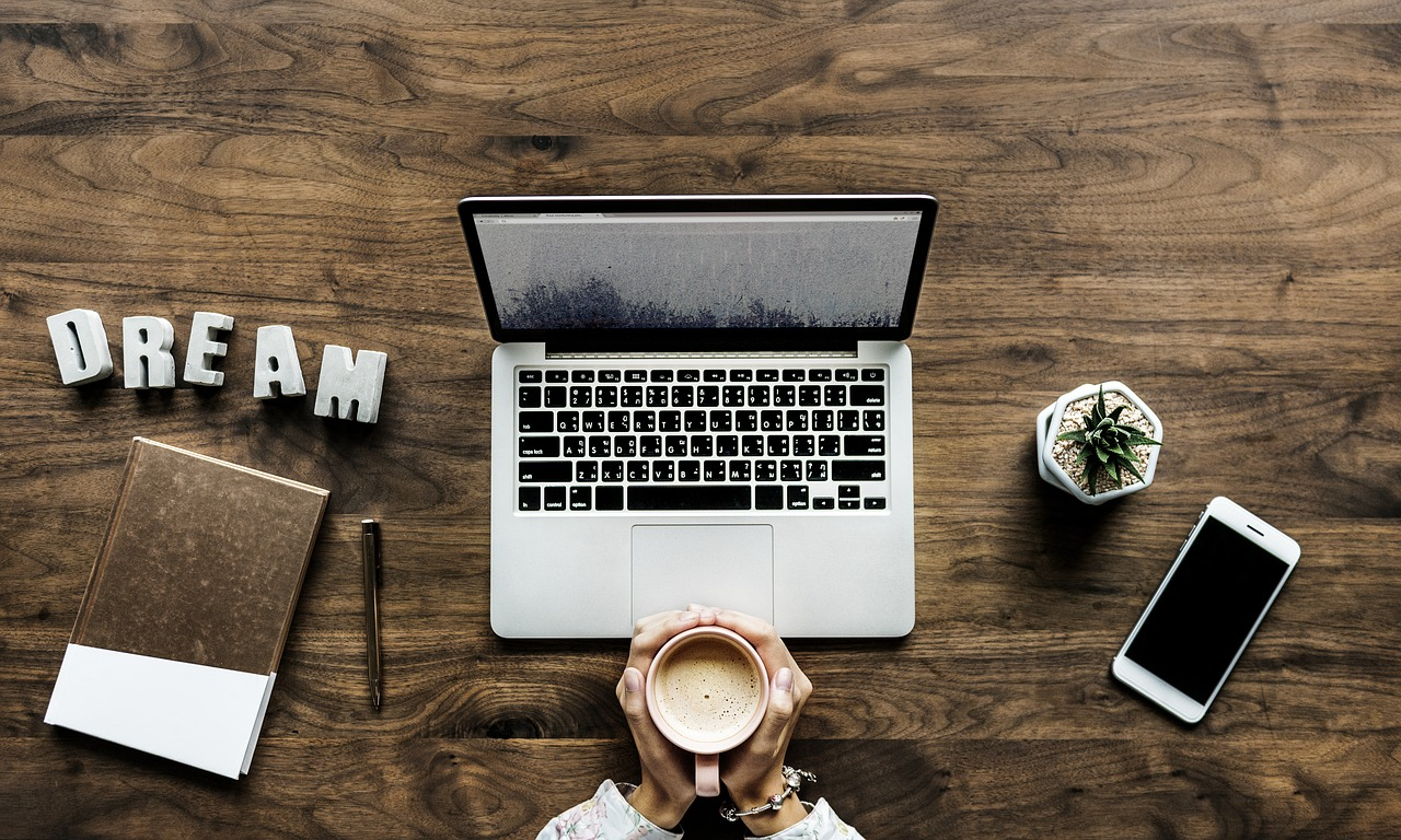 An open laptop on top of a beautifully styled raw wood desk, with hands holding a coffee cup near it, and the word DREAM spelled out in weird wood block cutouts on the table. Why are they there? Who was wooden cutout letters on their work desk? In any case, I enjoy the bullshit nature of this tableau.
